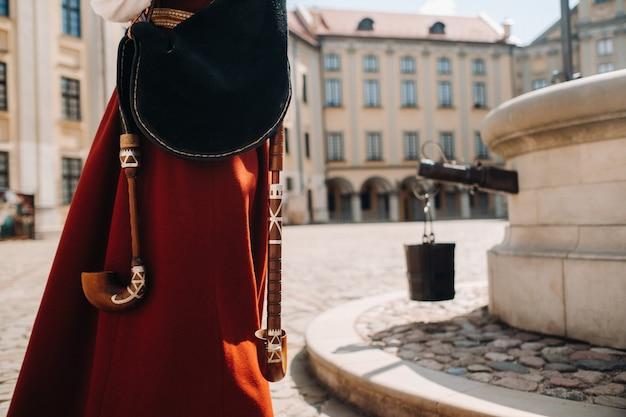 ネスヴィシ城の広場にある古い赤いドレスのクローズアップの男。ベラルーシのネスヴィシ城。 Premium写真