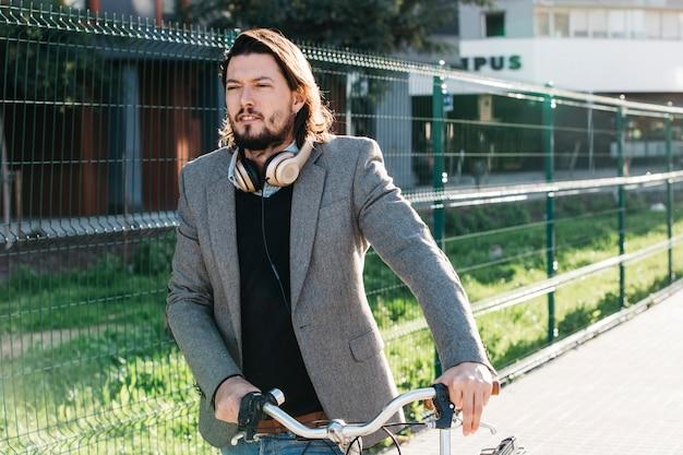 Мужчина в суде с наушниками на шее гуляет с велосипедом на улице Бесплатные Фотографии