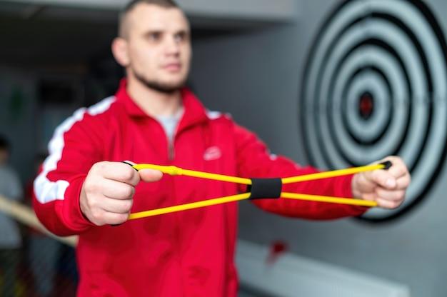 빨간 재킷을 입은 남자가 체육관에서 손을위한 운동 장비로 연습하고 있습니다. 무료 사진