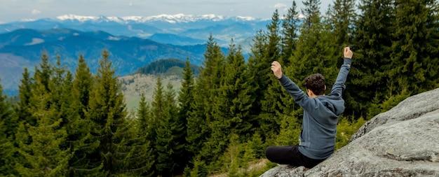 한 남자가 하늘을 배경으로 높은 산에서 승리를 축하하며 손을 들어 올립니다. 프리미엄 사진