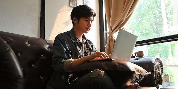 男はコンピューターのラップトップでタイプしていて、革のソファーに座っている間に膝を置く Premium写真