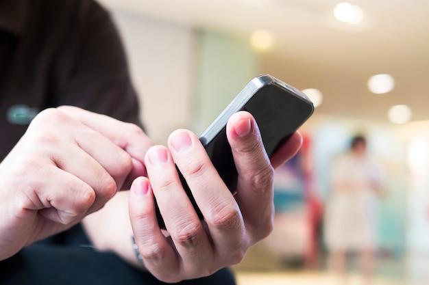 Человек использует телефон над красочным размытым светом боке в офисе и фоне людей Бесплатные Фотографии