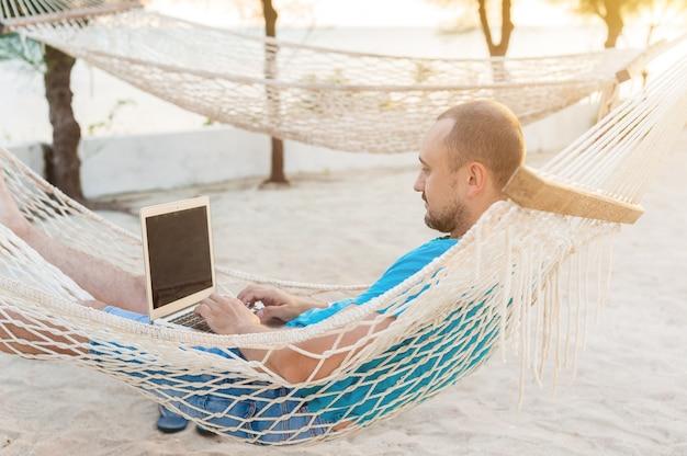 Человек лежал в гамаке с видом на океан Premium Фотографии