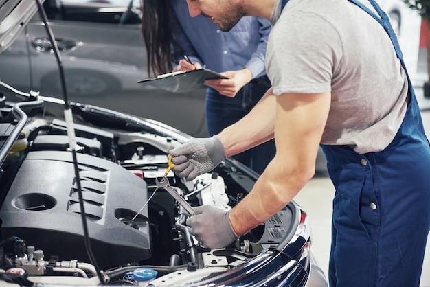 Мужчина-механик и женщина-клиент смотрят на капот машины и обсуждают вопросы ремонта Бесплатные Фотографии
