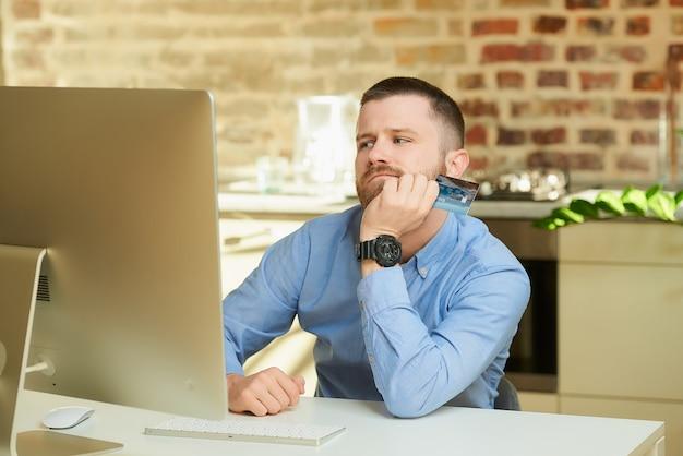 コンピューターの前でミスし、自宅でクレジットカードを持っている男性。 Premium写真