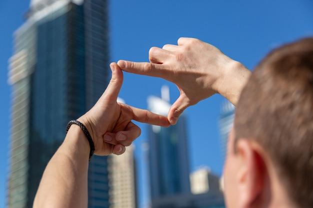 男性が将来の写真を計画し、指でフレームを作成します。 Premium写真