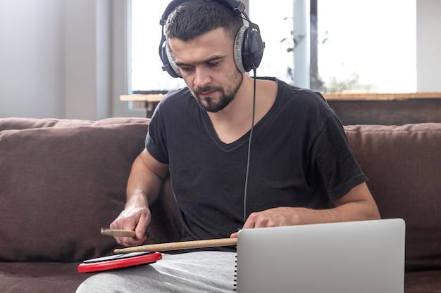 Мужчина играет в барабан и смотрит на экран ноутбука. концепция онлайн-уроков музыки, уроков по видеоконференцсвязи. Бесплатные Фотографии
