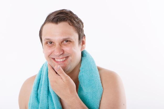 男は彼の顔にアフターシェーブを置きます。男は顔を撫でます。バスルームでの朝のトリートメント。コピースペース Premium写真