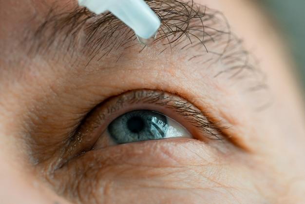 Мужчина закапывает глаза в глаза перед тем, как надеть контактные линзы. Premium Фотографии