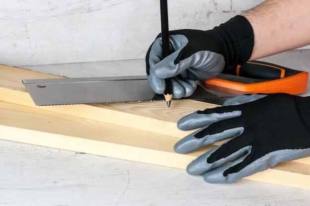 男は、のこぎりでさらに作業するために鉛筆で木の棒にマークを付けます。 diy at homeのコンセプト Premium写真