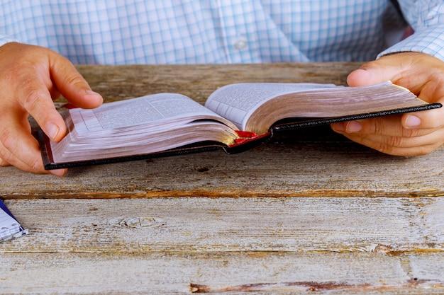 Мужчина читает библию крупным планом руки Premium Фотографии