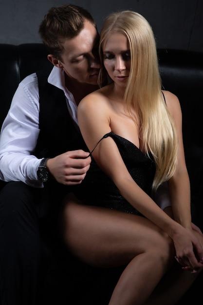 Мужчина снимает платье со своей очаровательной женщины, сидящей рядом с ним на диване. Premium Фотографии