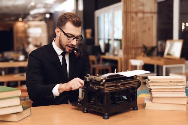 Мужчина сидит за столом со старой машинкой. Premium Фотографии