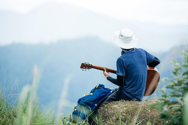 Человек, сидящий счастливо играть на гитаре в лесу один. Бесплатные Фотографии