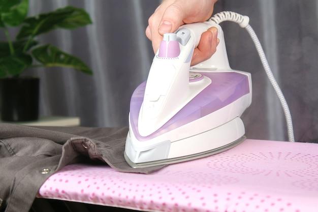 男がアイロン台で電気アイロンでリネンを撫でる Premium写真