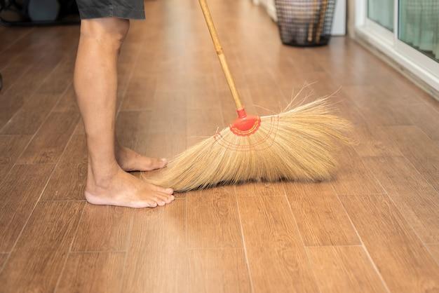 집에서 빗자루 청소를 사용하는 사람, 바닥 청소, 자연 장비 사용 프리미엄 사진