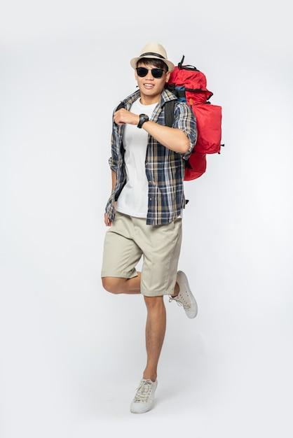 眼鏡をかけている男性が旅行に出かけ、帽子をかぶってバックパックを背負っています 無料写真