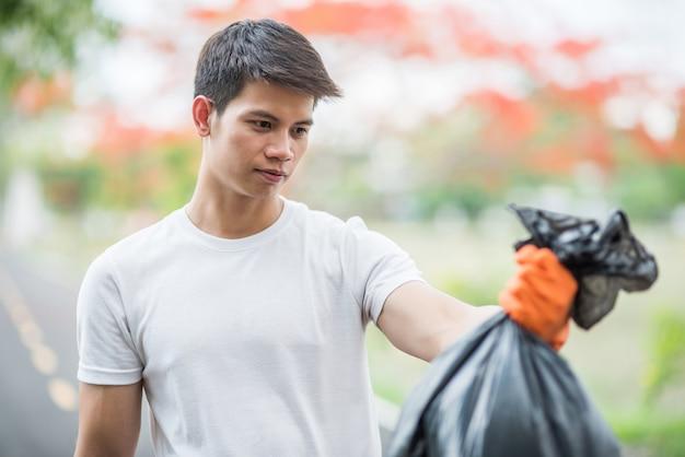 Мужчина в оранжевых перчатках собирает мусор в черной сумке. Бесплатные Фотографии