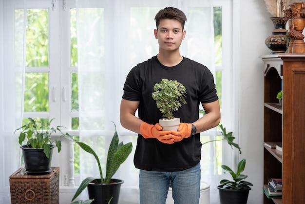 男はオレンジ色の手袋を着用し、家の中で植木鉢を保持するために立ちます。 無料写真