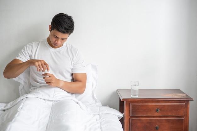 Мужчина, который плохо себя чувствует на кушетке и собирается принимать антибиотики. Бесплатные Фотографии