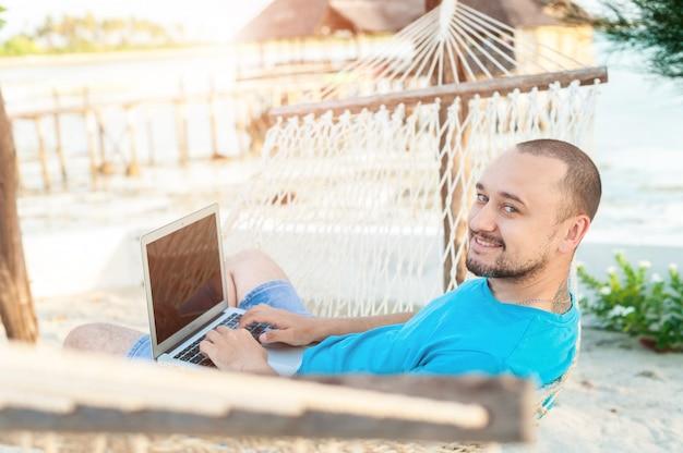 Мужчина с бородой лежит в гамаке с ноутбуком Premium Фотографии