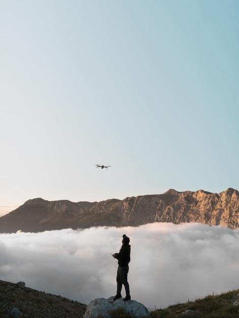雲の後ろを飛んでいる山でドローンを持つ男 無料写真