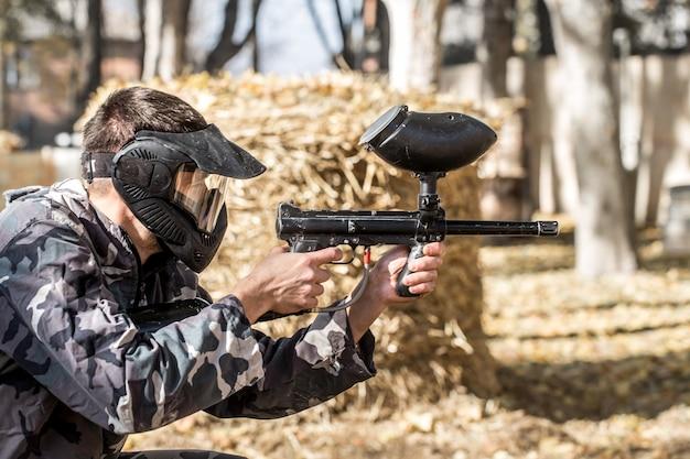 ペイントボールをしている銃を持った男。 無料写真