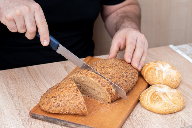 Мужчина ножом режет хлеб на деревянной доске. французские багеты. разные породы на деревянных фоне. Premium Фотографии