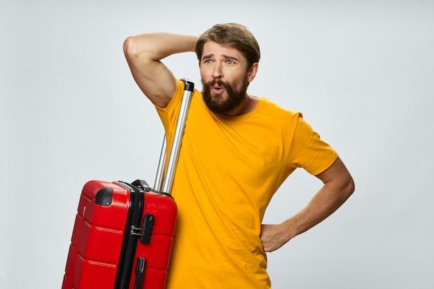 スーツケースを持った男が飛行機のフライトの動揺して感情の表情に遅れた Premium写真