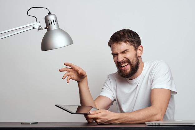 テーブルにタブレットを持っている男性は、明るい背景と鉄のランプに両手でジェスチャーします。高品質の写真 Premium写真