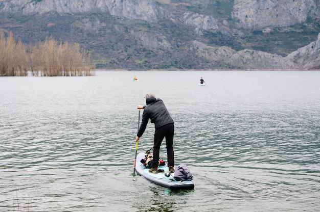 暖かい服を着た男が、ボードの上に荷物を持って山の湖でパドルサーフィンをする Premium写真
