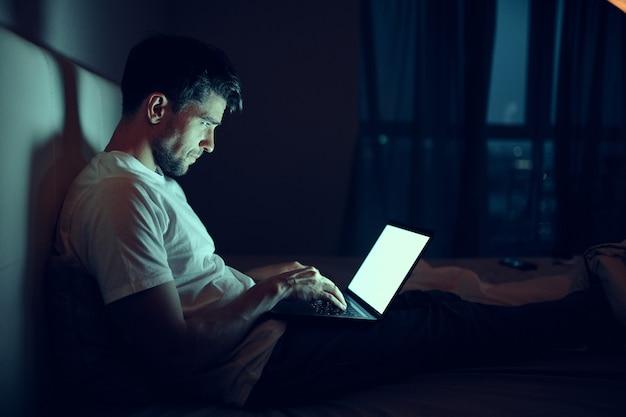 男はベッドでラップトップで働き、愛する女性は眠り、夜勤、反逆 Premium写真