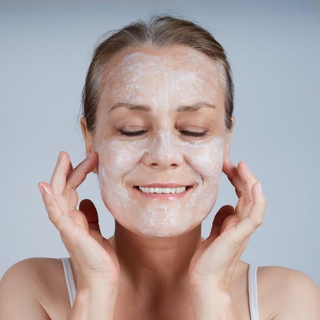 成熟した女性が顔に化粧用マスクを塗り、目を閉じます。老化肌のお手入れ。 Premium写真