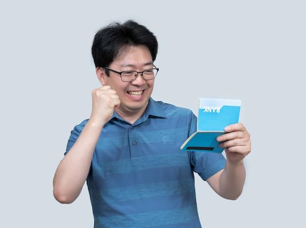 Азиатский мужчина средних лет держит банковскую книжку в руке Premium Фотографии