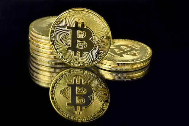 Зеркальное отражение золотых монет btc на черном фоне Premium Фотографии