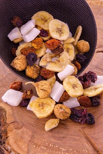 スライスしたドライフルーツとベリーのミックス、木の上の暗いカップからこぼれるナッツ Premium写真