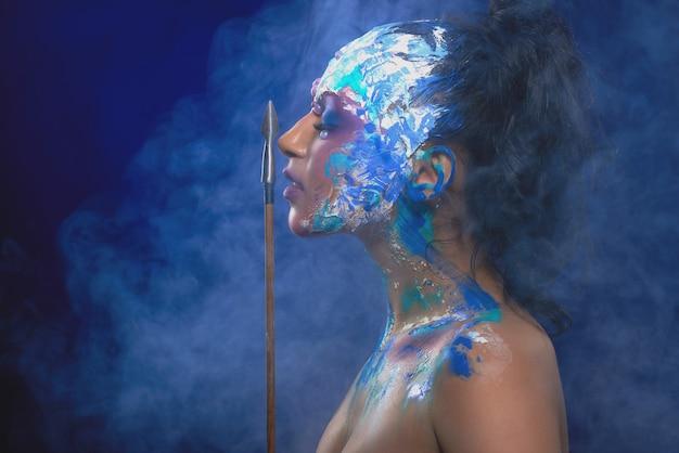 顔の近くに矢を放つ、派手で明るいメイクのモデル。彼女は濃い青の壁の煙の雲の中に立ち、ファンタジーのキャラクターのように見えます。 Premium写真