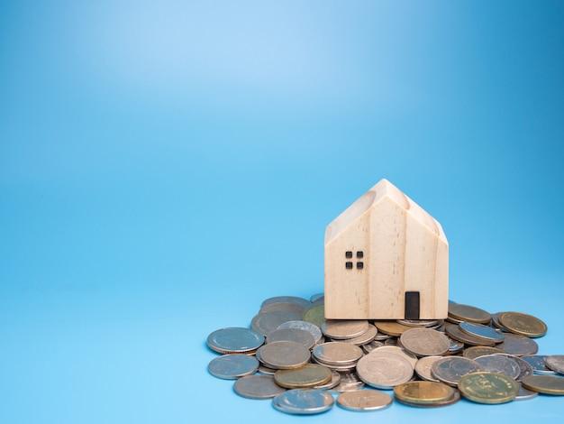 Модель деревянного дома и куча монет на синем Premium Фотографии