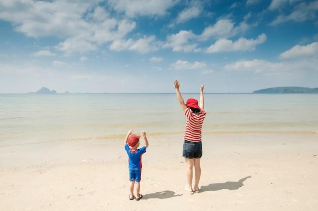 Мать и сын на пляже на открытом воздухе море и голубое небо Бесплатные Фотографии