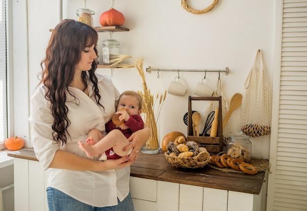 Мать держит на руках девочку с бутылкой сока на кухне Premium Фотографии