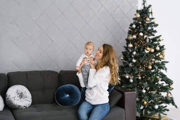 Мать держит своего маленького сына на руках и улыбается ему, сидя возле елки в гостиной дома. Premium Фотографии