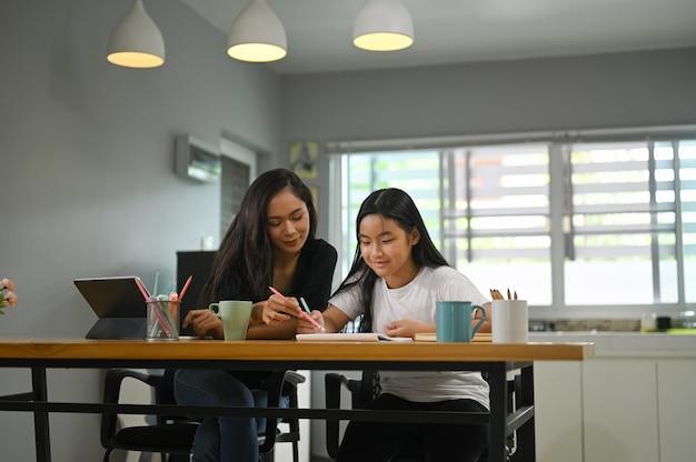 母親が娘と一緒に座って、木製のワーキングデスクで宿題を教えています。 Premium写真
