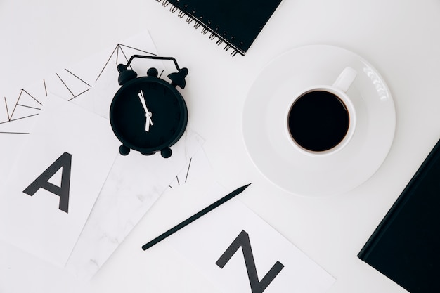 目覚まし時計;鉛筆;日記;コーヒーカップと白い背景の上の手紙aとnの紙 無料写真