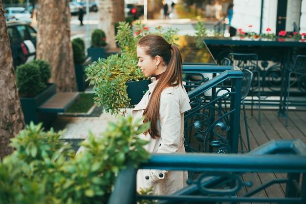 멋진 젊은 아가씨가 낮에 도시의 외부 카페에서 나가고 있습니다. 프리미엄 사진