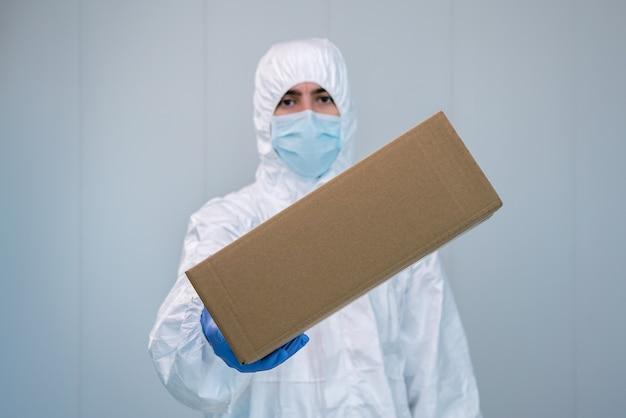 Медсестра в защитном костюме показывает ящик одной рукой в больнице. медицинский работник получает медикаменты для борьбы с коронавирусом Premium Фотографии