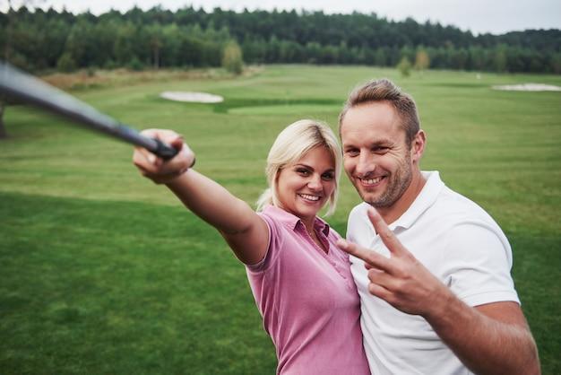 한 쌍의 골퍼가 세피 폴과 같은 스틱을 사용하여 골프 코스에서 사진을 찍습니다. 프리미엄 사진