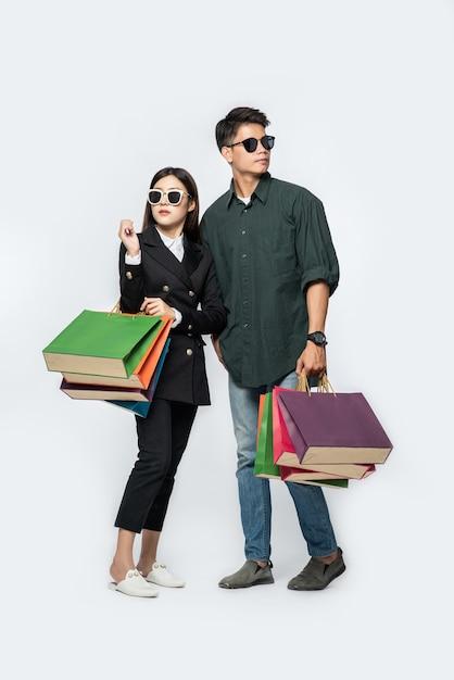 Пара мужчина и женщина в очках несли много бумажных пакетов для покупок Бесплатные Фотографии