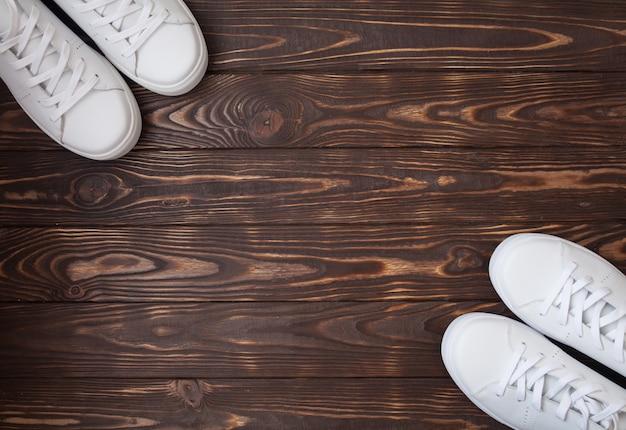 木製の白いキャンバスシューズのペア。茶色の背景に白のスニーカー。 Premium写真
