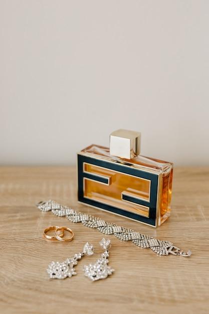 Флакон духов, браслет, серьги-гвоздики и обручальные кольца на деревянном столе у светлой стены. Premium Фотографии
