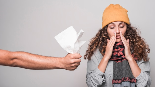 A person giving tissue paper to sick woman suffering from flu Free Photo